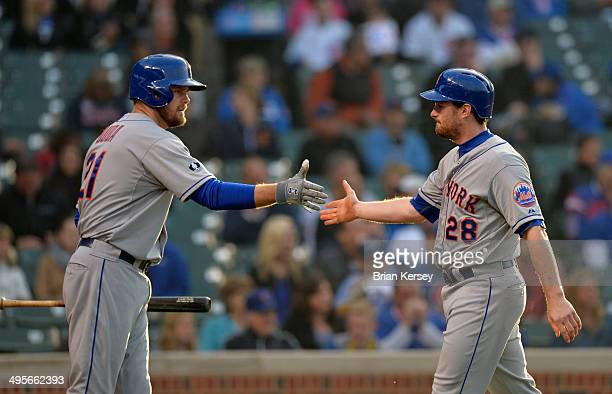 Lucas Duda of the New York Mets congratulates Daniel Murphy after Murphy scored on a fielding error by Starlin Castro of the Chicago Cubs on a ball...