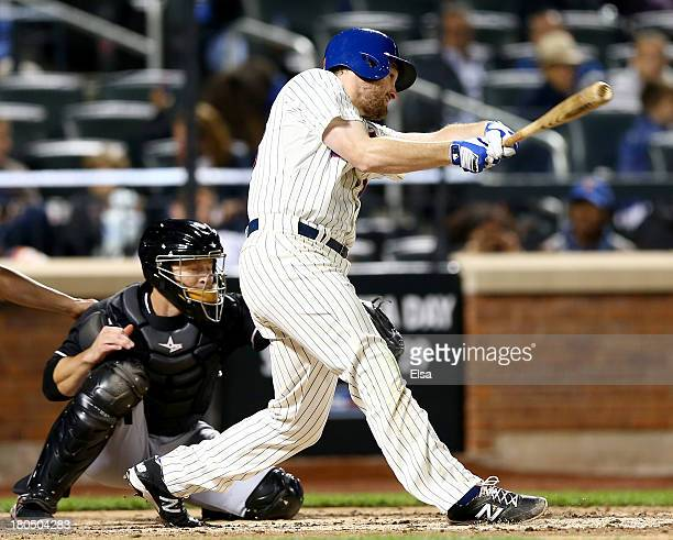 Lucas Duda of the New York Mets hits a three run homer as Koyie Hill of the Miami Marlins catches on August 13, 2013 at Citi Field in the Flushing...
