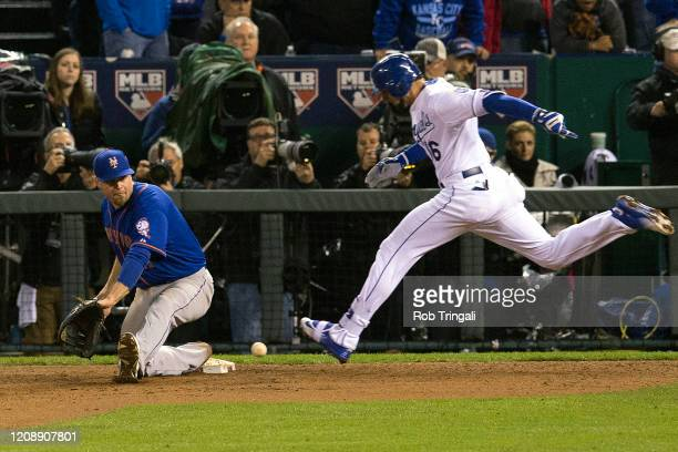Lucas Duda of the New York Mets stretches for a ball as Paulo Orlando of the Kansas City Royals runs to first base during Game 1 of the 2015 World...