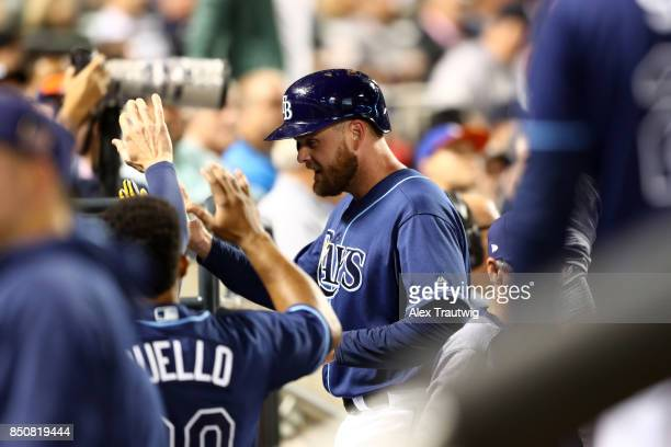 Lucas Duda of the Tampa Bay Rays celebrates with teammates in the dugout after scoring during the game against the New York Yankees at Citi Field on...