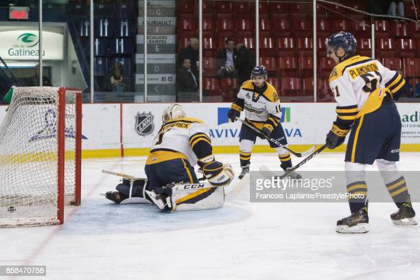 Lucas Fitzpatrick Antoine Demers and Alex Plamondon of the Shawinigan Cataractes looks on as the puck sits in the net after a goal by the Gatineau...