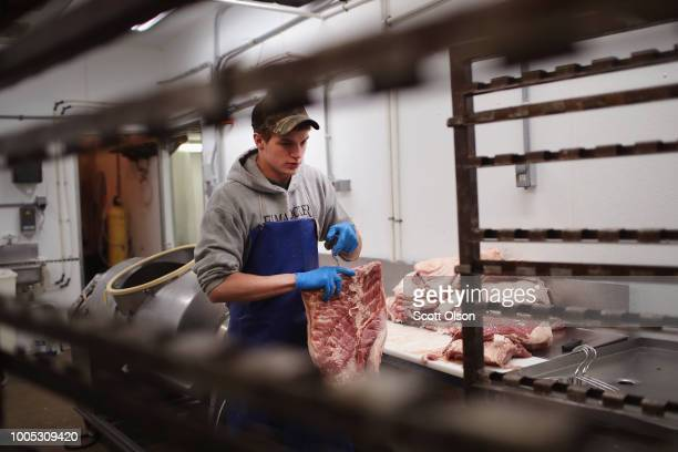 Lucas Gebel makes bacon while helping to process hogs at Elma Locker Grocery on July 25 2018 in Elma Iowa The locker custom butchers hogs and cattle...