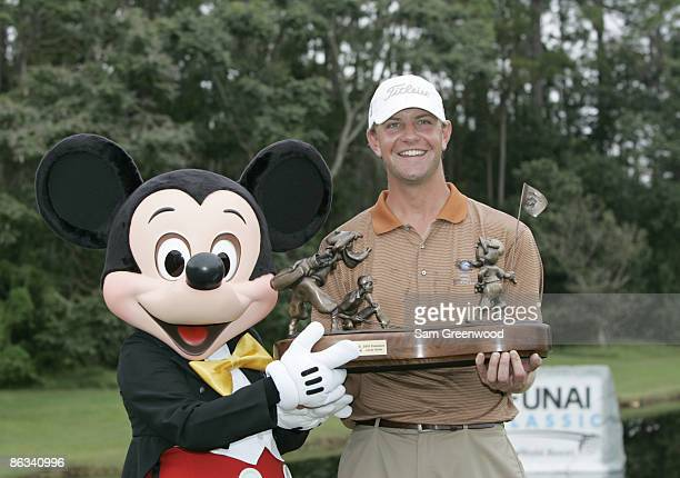 Lucas Glover and Mickey Mouse hold the trophy after the final round of the Funai Classic held on the Magnolia course at Walt Disney World Resort in...