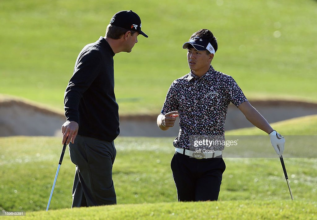 Lucas Glover (L) and Ryo Ishikawa of Japan talk on the first hole during the first round of the Humana Challenge In Partnership With The Clinton Foundationat at the Palmer Private Course at PGA West on January 17, 2013 in La Quinta, California.