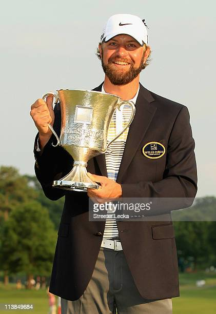 Lucas Glover poses with the trophy after defeating Jonathan Byrd on the first playoff hole during the final round of the Wells Fargo Championship at...