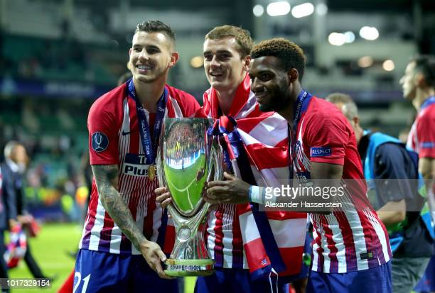 Lucas Hernandez Antoine Griezmann and Thomas Lemar of Atletico Madrid celebrate with the trophy following the UEFA Super Cup between Real Madrid and...