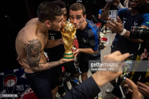 Lucas Hernandez Djibril Sidibe and Antoine Griezmann of France kiss the World Cup Trophy in the dressing room following their victory in the 2018...