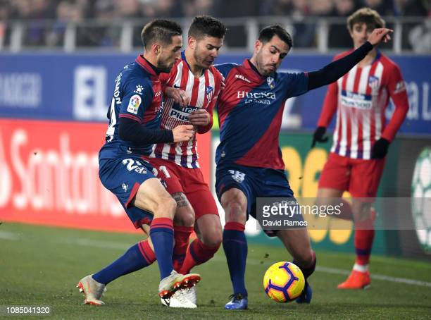 Lucas Hernandez of Atletico Madrid battles for possesion with Enric Gallego and Pablo Insua of SD Huesca during the La Liga match between SD Huesca...