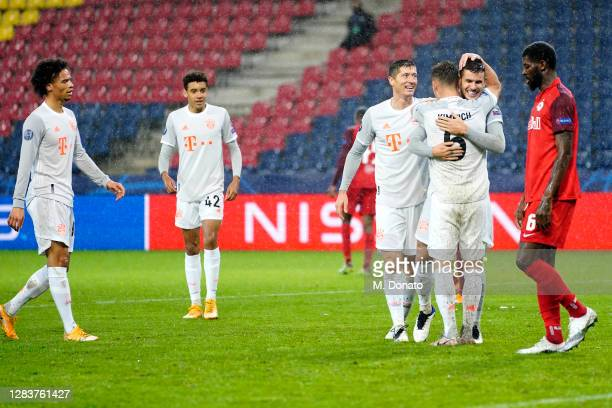 Lucas Hernandez of FC Bayern Muenchen celebrates with team mates Joshua Kimmich and Robert Lewandowski after scoring his team's sixth goal during the...