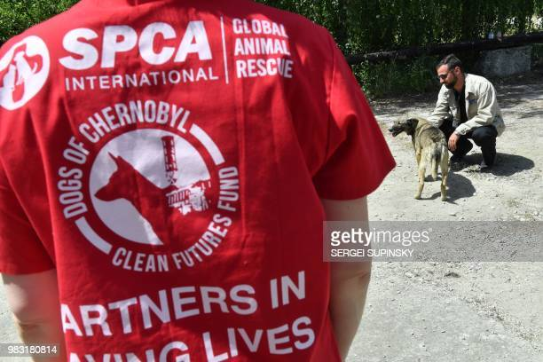 Lucas Hixson cofounder of Clean Futures Fund strokes a stray dog outside the improvised animals hospital based just near the Chernobyl power plant on...