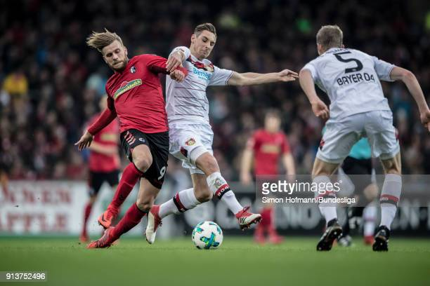 Lucas Hoeler of Freiburg is tackled by Dominik Kohr of Leverkusen during the Bundesliga match between SportClub Freiburg and Bayer 04 Leverkusen at...