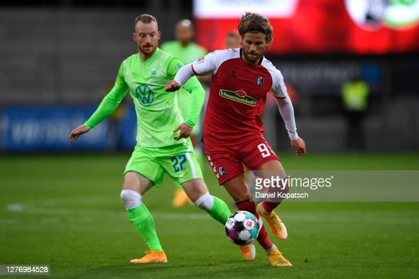 Lucas Holer of Sport-Club Freiburg is put under pressure by Maximilian Arnold of VfL Wolfsburg during the Bundesliga match between Sport-Club...
