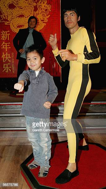 Lucas Hui poses next to a waxwork model of Bruce Lee which forms part of a temporary attraction starring eight of Chinas top celebrities in...