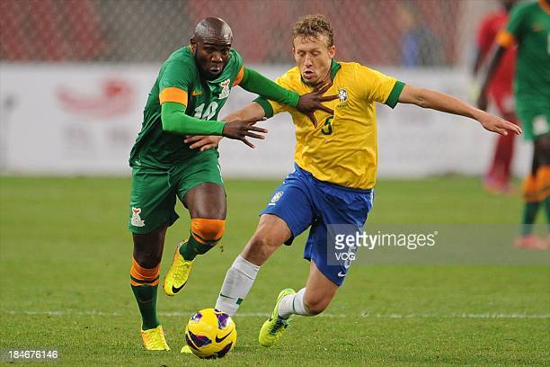 Lucas Leiva of Brazil and Fwayo Tembo of Zambia battle for the ball during the international friendly match between Brazil and Zambia at Beijing...