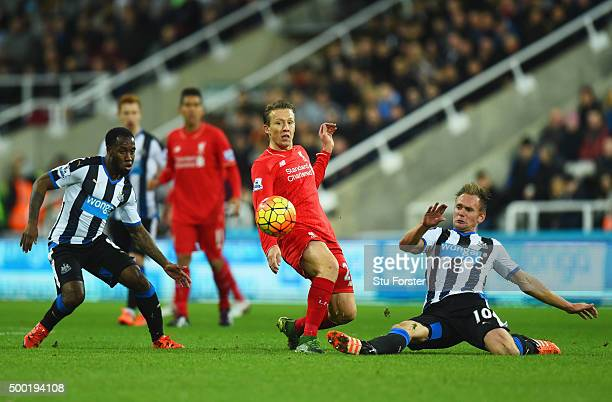 Lucas Leiva of Liverpool battles with Vurnon Anita and Siem de Jong of Newcastle United during the Barclays Premier League match between Newcastle...