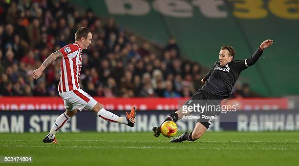 Lucas Leiva of Liverpool competes with Glenn Whelan of Stoke City during the Capital One Cup semi final first leg match between Stoke City and...