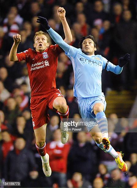 Lucas Leiva of Liverpool goes up with David Silva of Manchester City during a Barclays Premier League match between Liverpool and Manchester City at...