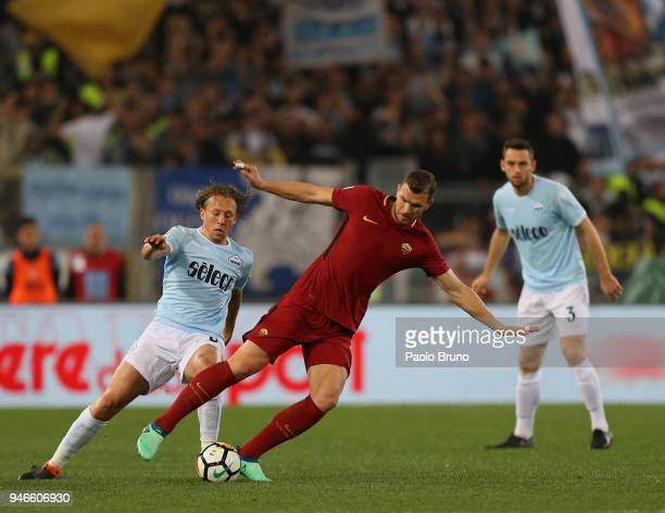 Lucas Leiva of SS Lazio competes for the ball with Edin Dzeko of AS Roma during the serie A match between SS Lazio and AS Roma at Stadio Olimpico on...