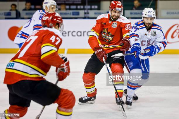 Lucas Lessio of HC Kunlun Red Star and Vyacheslav Voynov of SKA Saint Petersburg vie for the puck during the 2017/18 Kontinental Hockey League...