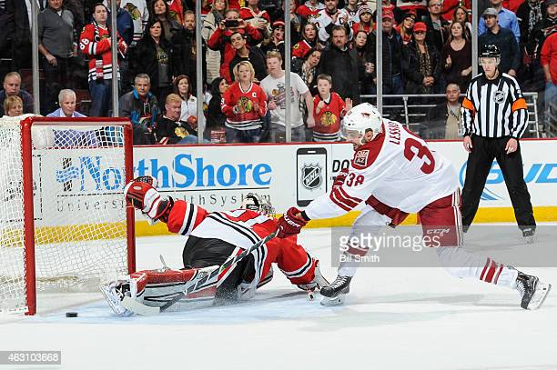 Lucas Lessio of the Arizona Coyotes scores on goalie Antti Raanta of the Chicago Blackhawks in the shootout during the NHL game at the United Center...