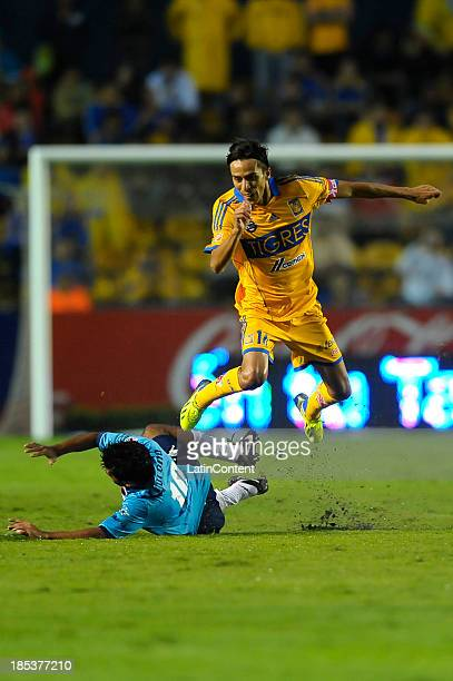 Lucas Lobos of Tigres fights for the ball with Walter Erviti of Atlante during a match between Tigres UANL and Atlante as part of the Apertura 2013...
