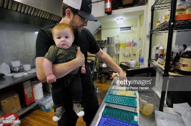 Lucas McNelly holds his fivemonthold son Rhys while making lip balm at Long Winter Soap Co Tuesday May 9 2017