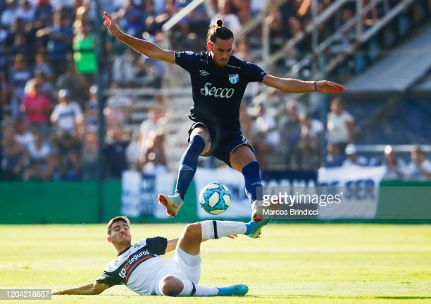 Lucas Melano of Atletico Tucuman jumps over Matias Melluso of Gimnasia y Esgrima La Plata as they fight for the ball during a match between Gimnasia...