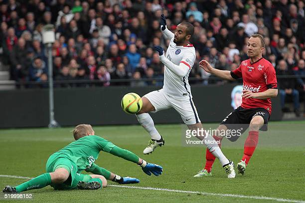 Lucas Moura of Paris SaintGermain challenges for the ball with Jonas Lossl of Guingamp during the French League 1 match between EA Guingamp and Paris...