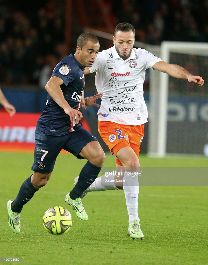 Lucas Moura of Paris Saint-Germain in action with Jamel Saihi of Montpellier Herault SC during the French Ligue 1 between Paris Saint-Germain FC and Montpellier Herault SC at Parc Des Princes on December 20, 2014 in Paris, France.