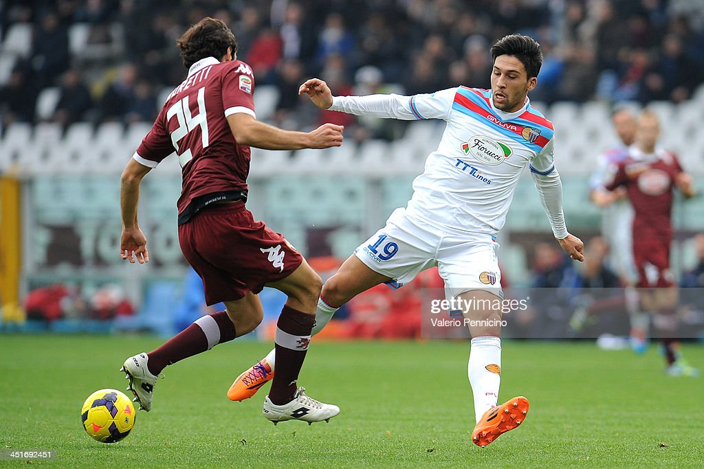 Lucas Nahuel Castro (R) of Calcio Catania is tackled by Emiliano Moretti of Torino FC during the Serie A match between Torino FC and Calcio Catania at Stadio Olimpico di Torino on November 24, 2013 in Turin, Italy.
