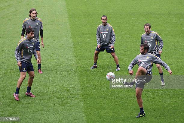 Lucas Neill is watched by Mile Jedinak Matthew Spiranovic Scott McDonald and Luke Wilkshire during the Australia Training session at the Cardiff City...