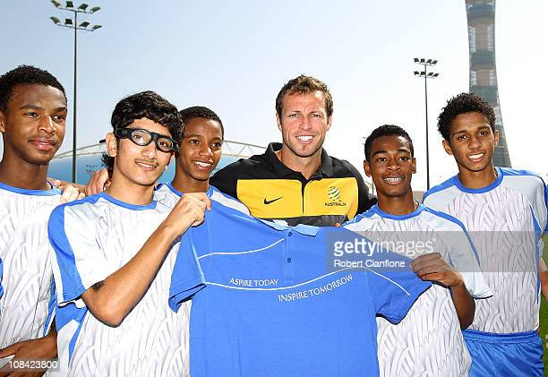 Lucas Neill of the Australian Socceroos poses with a junior football team as he visits the ASPIRE Academy for Sports Excellence on January 27 2011 in...