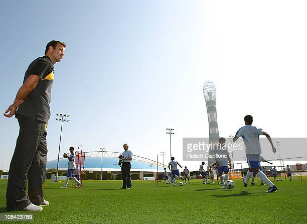 Lucas Neill of the Australian Socceroos watches over a junior football training session as he visits the ASPIRE Academy for Sports Excellence on...