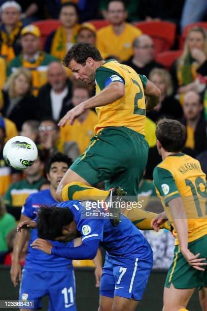 Lucas Neill of the Socceroos jumps over Datsakorn Thornlao of Thailand to head the ball during the Asian Qualifying 2014 FIFA World Cup match between...