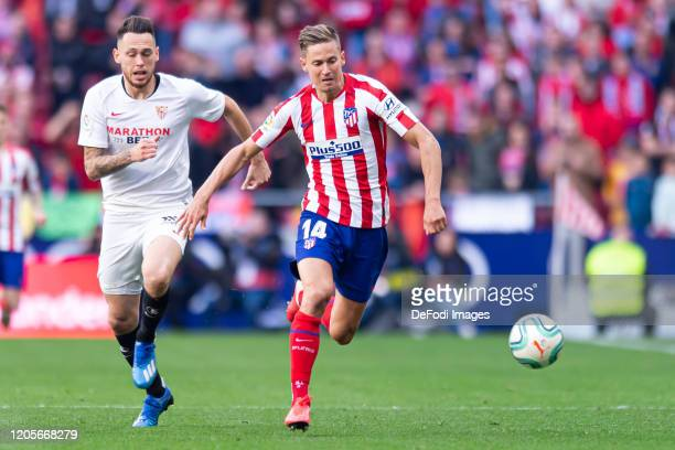 Lucas Ocampos of Sevilla FC and Marcos Llorente of Atletico de Madrid battle for the ball during the Liga match between Club Atletico de Madrid and...
