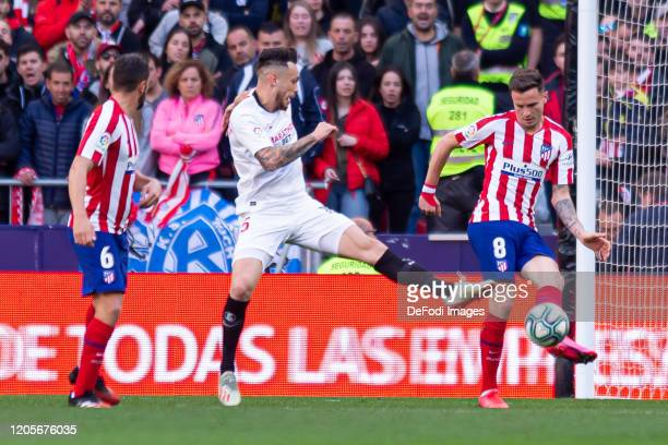 Lucas Ocampos of Sevilla FC and Saul Niguez of Atletico de Madrid battle for the ball during the Liga match between Club Atletico de Madrid and...