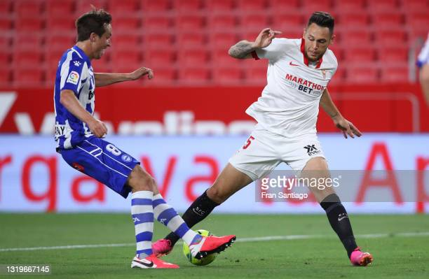 Lucas Ocampos of Sevilla FC battles for possession with Tomas Pina of Deportivo Alaves during the La Liga Santander match between Sevilla FC and...