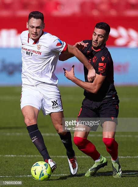 Lucas Ocampos of Sevilla FC competes for the ball with Mikel Merino of Real Sociedad during the La Liga Santander match between Sevilla FC and Real...