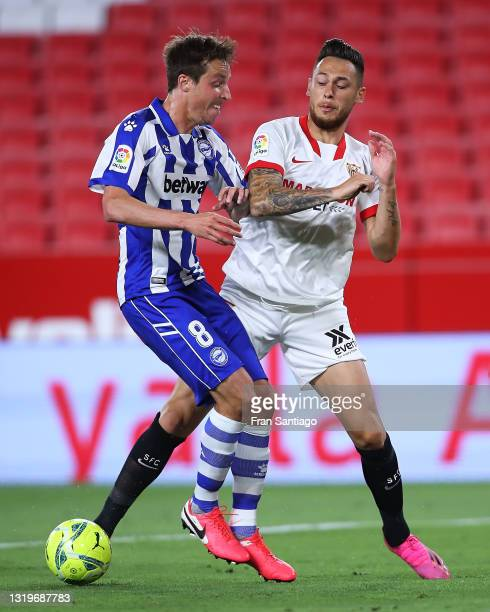 Lucas Ocampos of Sevilla FC competes for the ball with Tomas Pina of Deportivo Alaves during the La Liga Santander match between Sevilla FC and...