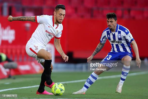 Lucas Ocampos of Sevilla FC is put under pressure by Ximo of Deportivo Alaves during the La Liga Santander match between Sevilla FC and Deportivo...