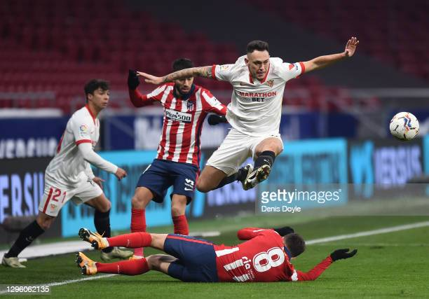 Lucas Ocampos of Sevilla FC leaps over Saul Niguez of Atletico de Madrid during the La Liga Santander match between Atletico de Madrid and Sevilla FC...