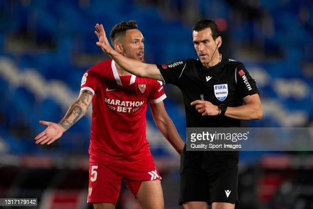 Lucas Ocampos of Sevilla FC pleads to referee Juan Martinez Munuera during the La Liga Santander match between Real Madrid and Sevilla FC at Estadio...