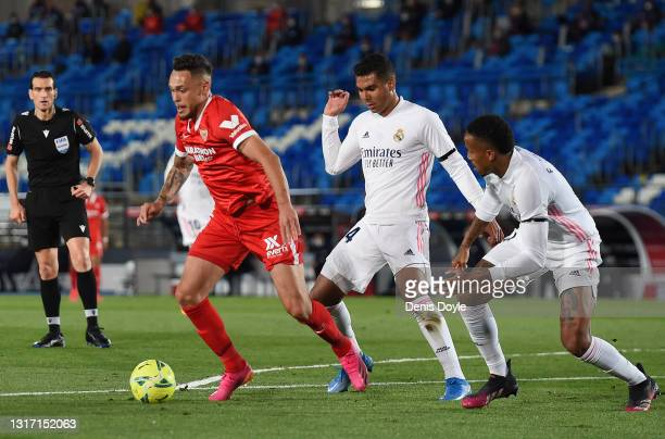Lucas Ocampos of Sevilla runs with the ball whilst under pressure from Casemiro and Eder Militao of Real Madrid during the La Liga Santander match...