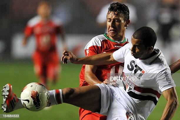 Lucas of Brazil's Sao Paulo, vies for the ball with Arnaldo Vera of Ecuador's Liga de Loja, during their 2012 Copa Sudamericana football match held...