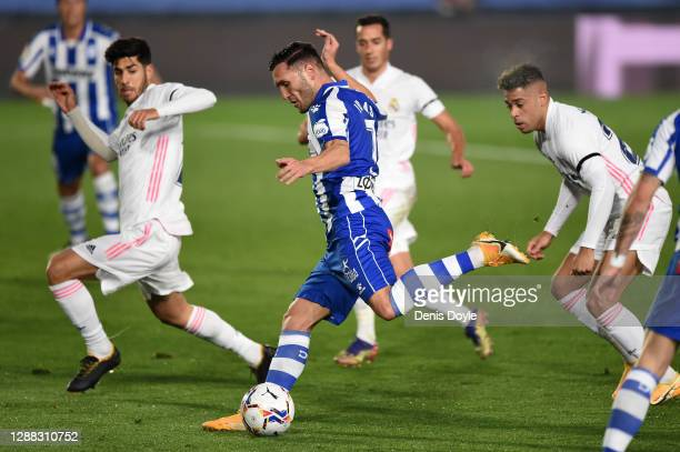 Lucas of Deportivo Alaves shoots past Marco Asensio of Real Madrid and misses a chance during the La Liga Santander match between Real Madrid and...