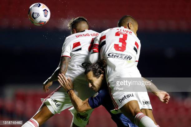 Lucas Orban of Racing Club jumps for the ball with Diego Costa and Bruno Alves of Sao Paulo during a match between Sao Paulo and Racing Club as part...