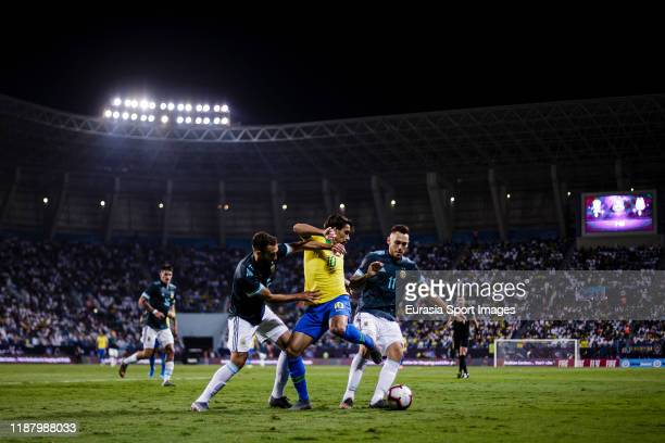 Lucas Paqueta of Brazil fights for the ball with German Pezzella and Lucas Ocampos of Argentina during the international friendly match between...