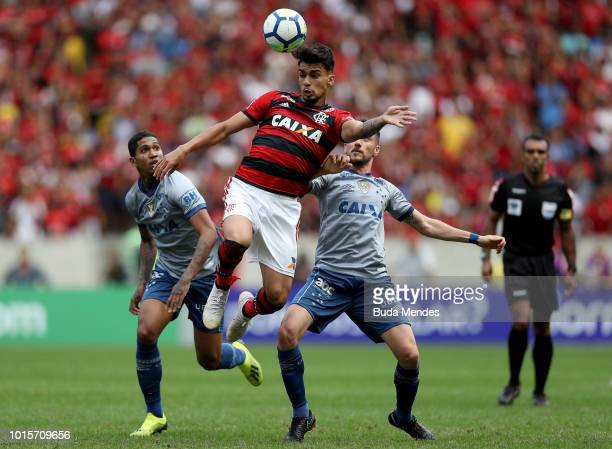 Lucas Paqueta of Flamengo struggles for the ball with Raniel and Marcelo Hermes of Cruzeiro during a match between Flamengo and Cruzeiro as part of...