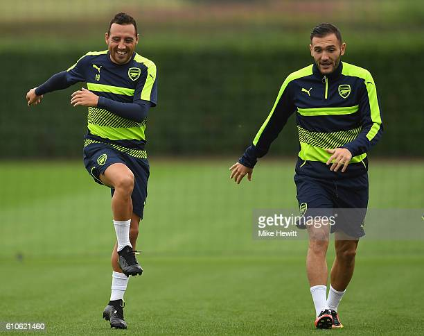 Lucas Perez and Santi Cazorla of Arsenal share a joke during an Arsenal training session ahead of the Champions League Group A match between Arsenal...