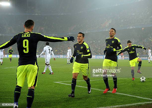 Lucas Perez celebrates scoring the 2nd Arsenal goal with Alexis Sanchez and Kieran Gibbs during the UEFA Champions League match between FC Basel and...